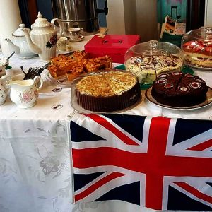 table decorated with union flag laid with lots of delicious cakes and vintage tea set